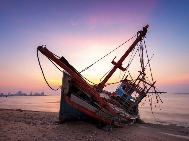 a sailboat shipwrecked on the beach