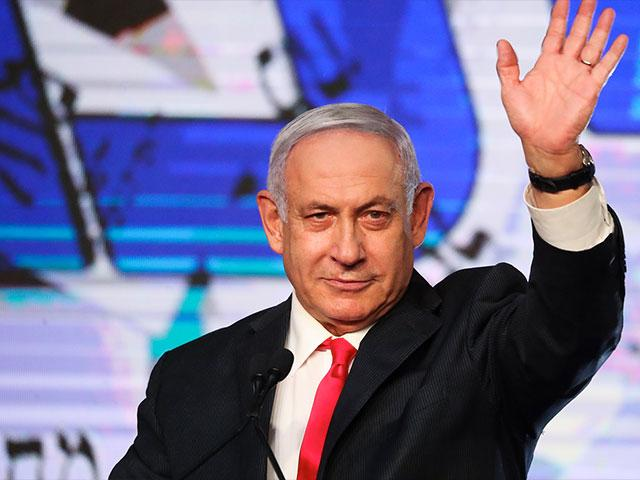 Israeli Prime Minister Benjamin Netanyahu waves to his supporters after the first exit poll results for the Israeli parliamentary elections at his Likud party's headquarters in Jerusalem, Wednesday, March. 24, 2021. (AP Photo/Ariel Schalit)