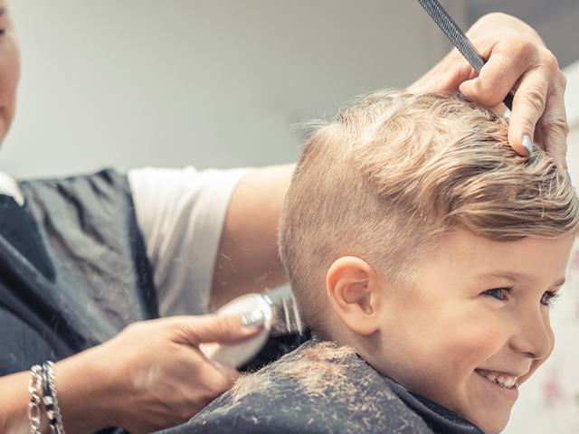 boy getting a buzz haircut at the salon