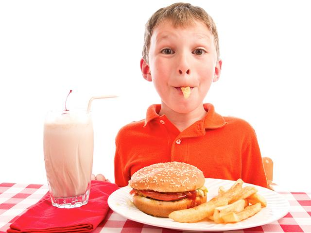 young boy eating a french fry with a chocolate milk shake