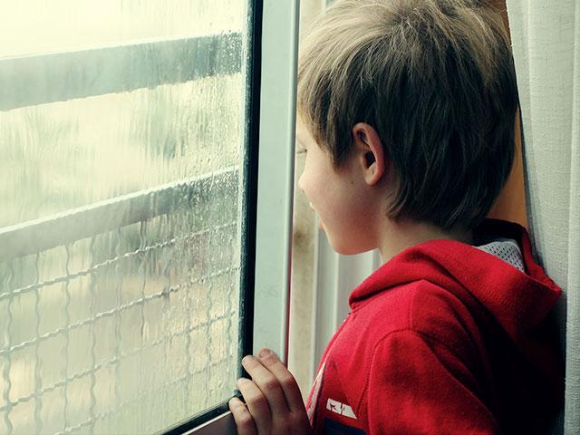 boy at storm door glass
