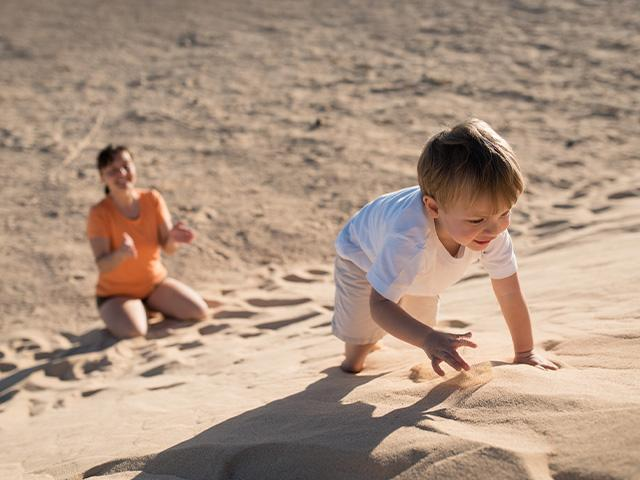 boy climbing a sand dune with his mother at the base of it encouraging him