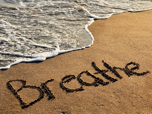 the word breathe written in the sand