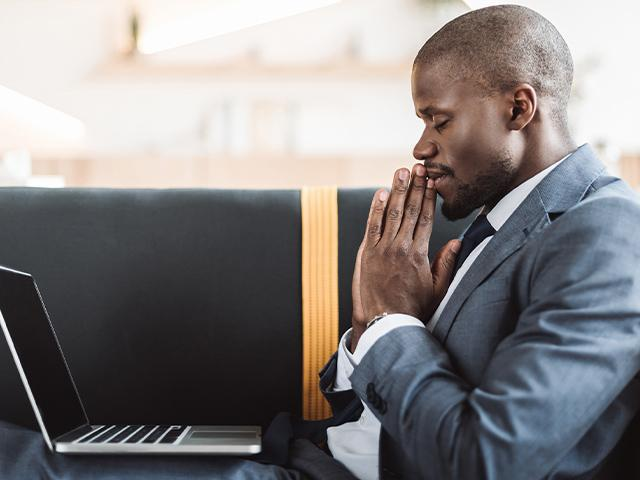businessman saying a prayer with his laptop open and on his lap