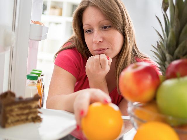 woman looking in the refrigerator at cake and fruit
