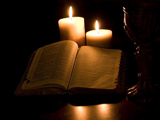 dark background and a Bible with candlelight