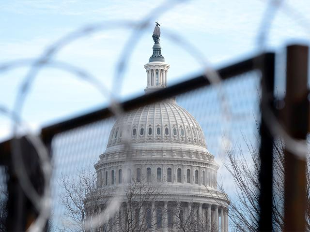 The U.S. Capitol is seen through a fence with barbed wire during the impeachment trial of former President Donald Trump at Capitol Hill in Washington, Tuesday, Feb. 9, 2021. (AP Photo/Jose Luis Magana)