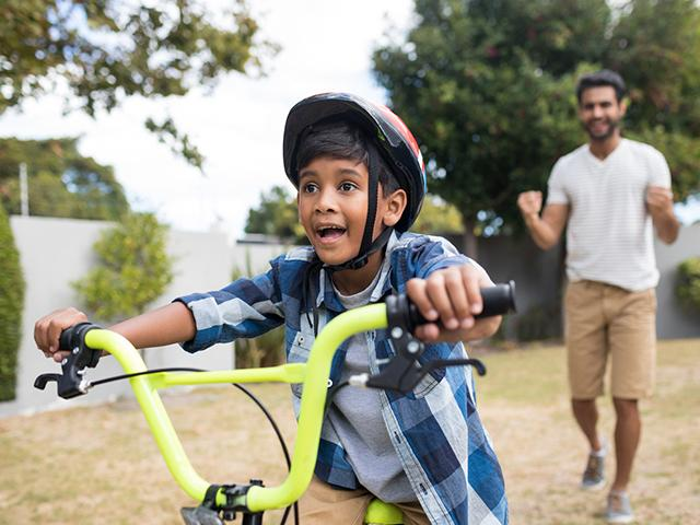 child with father learning to ride a bicycle