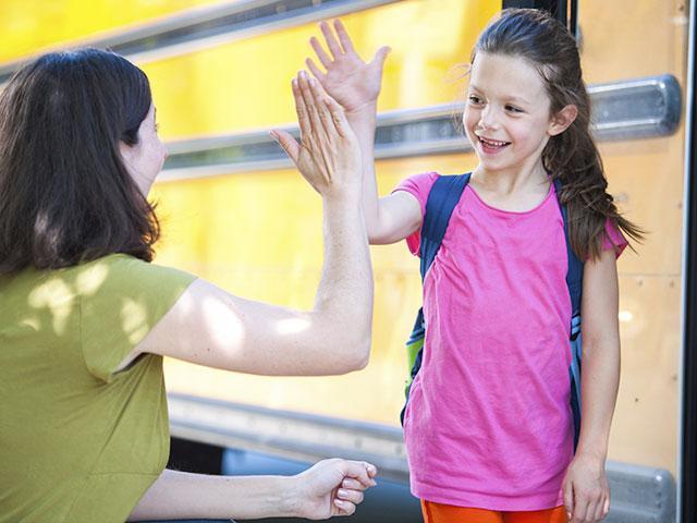 Girl at school bus stop
