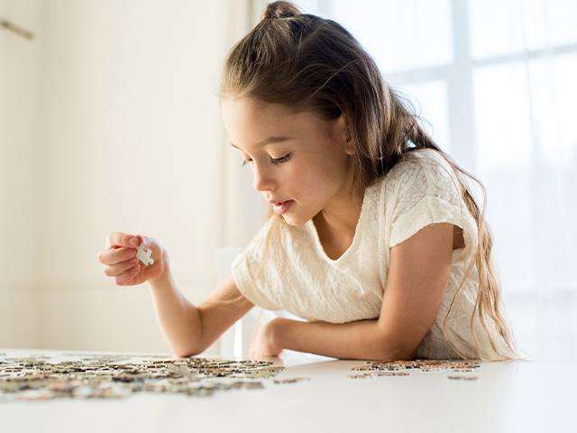 child working on a jigsaw puzzle