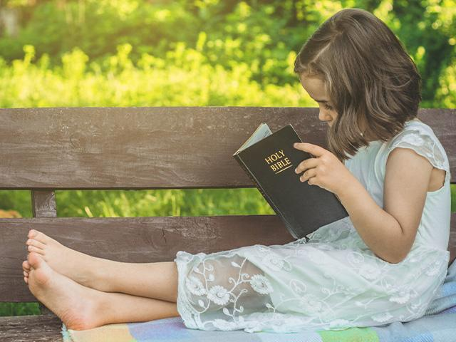 child-reading-bible-outdoors