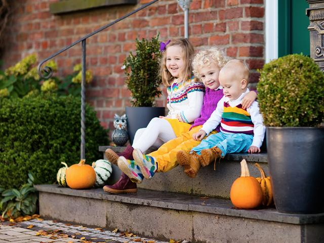 children sitting on the steps of a house with pumpkins