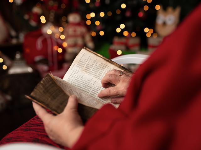 senior person sitting near christmas tree reading the Bible