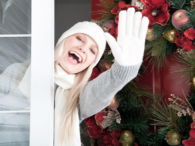 Woman waving from her front door wearing Christmas clothing