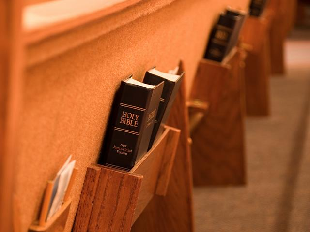 a church pew with Bibles in the book holders