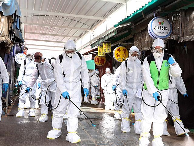 Workers wearing protective suits spray disinfectant as a precaution against the coronavirus at a market in Bupyeong, South Korea, Monday, Feb. 24, 2020. South Korea reported another large jump in new virus cases Feb. 24 (Lee Jong-chul/Newsis via AP)