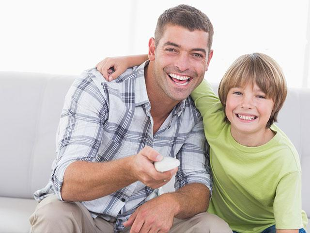 Father and son watching television
