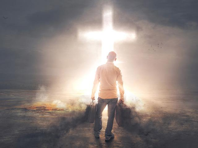 a man walking through darkness heading to light coming from a cross