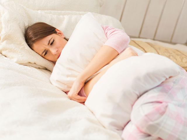 Depressed woman lying in bed