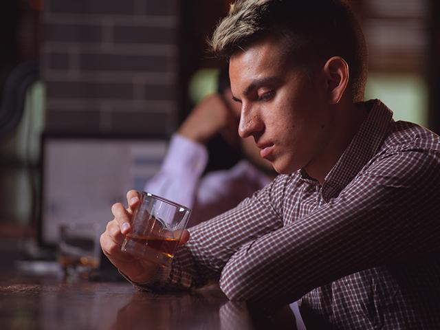 man sitting at bar staring into his glass