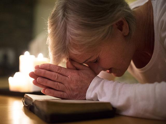 woman praying with head on her Bible and prostrate