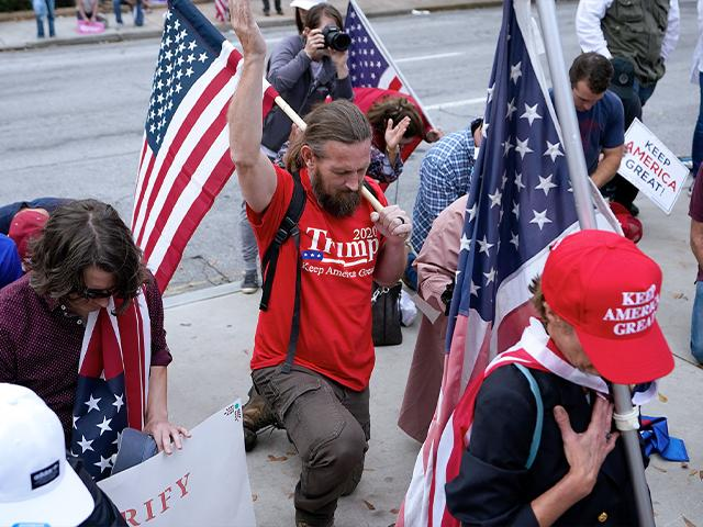 Supporters of President Donald Trump pray near the state capitol, Saturday, Nov. 7, 2020 in Atlanta.