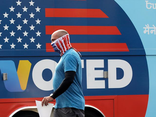 A voter casts a ballot during coronavirus quarantines (AP Photo/Marcio Jose Sanchez)