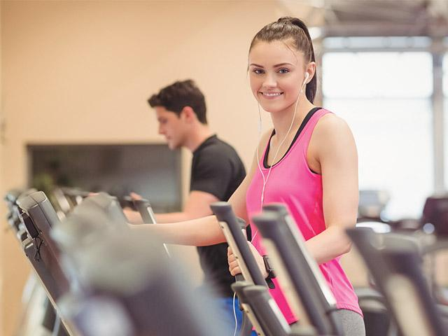 young woman working out at a gym and wearing earbuds