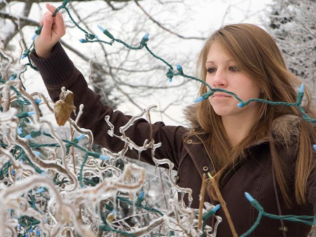 woman untangling exterior christmas lights