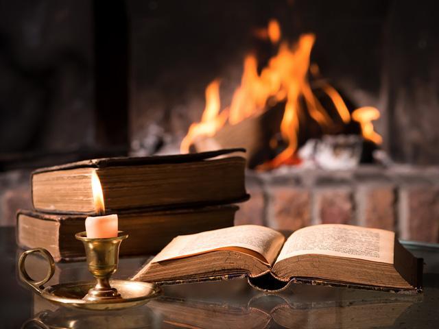 open Bible near a fireplace