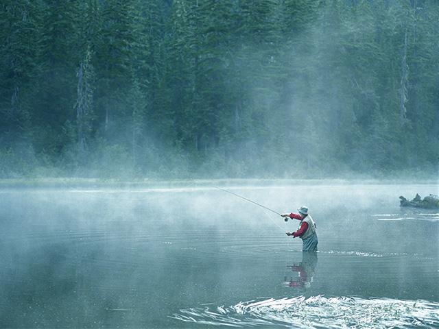 fog over a lake with a man fishing in waders