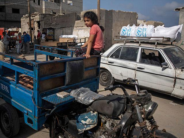 A Palestinian girl sits on an auto rickshaw next to a car loaded with sacks of flour received from UNRWA at a warehouse in Gaza City, Wednesday, Sept. 30, 2020. (AP Photo/Khalil Hamra)