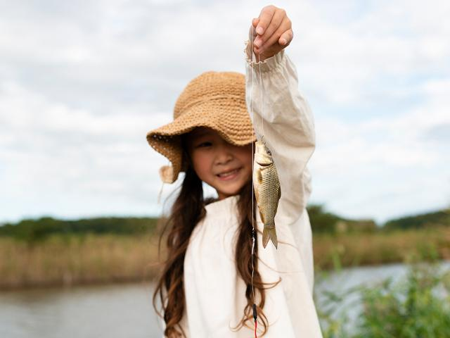 little girl holding up the fish she caught