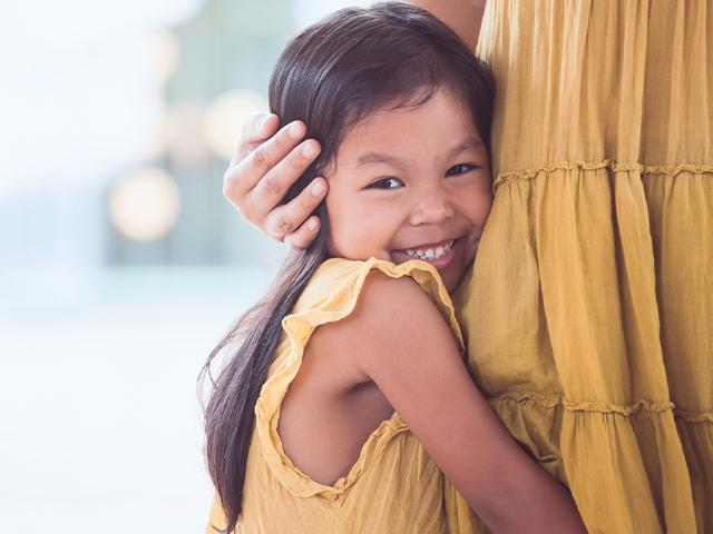 little girl hugging a woman from the side