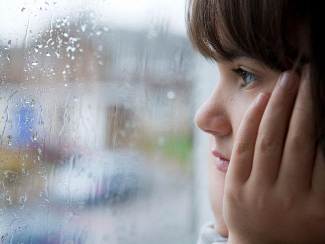 Girl looking out at the rain