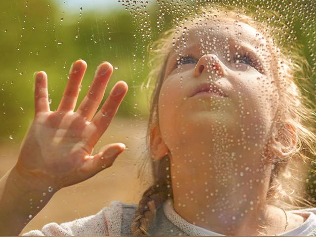 girl watching water droplets roll down a window