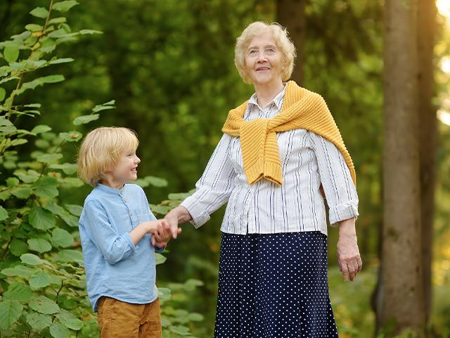 grandmother and grandson holding hands on a path outside