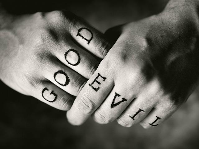 two hands with good written on one and evil on the other