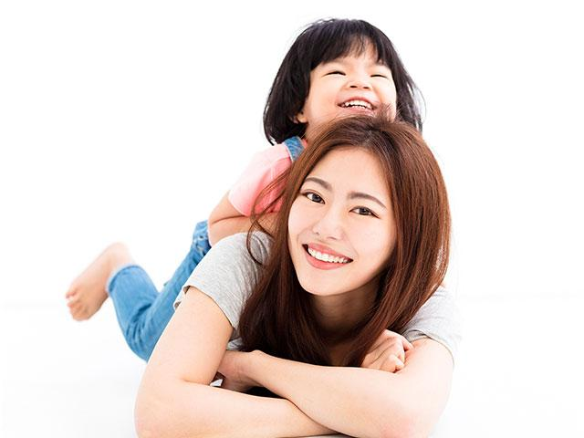 Happy mother playing with little girl