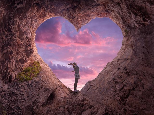 woman praising God in a heart-shaped cave opening