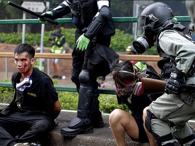 Riot police detain protesters near Hong Kong Polytechnic University in Hong Kong, Monday, Nov. 18, 2019. (AP Photo/Achmad Ibrahim)