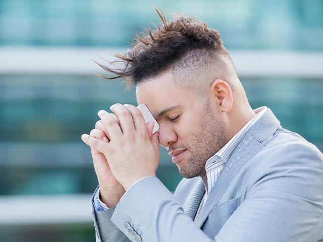 man with eyes closed praying and hoping with his phone to his head