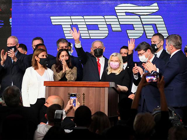 Israeli Prime Minister Benjamin Netanyahu, center,  waves after delivering a speech to supporters following the announcement of exit polls of the Israeli elections. Wednesday, March. 24, 2021. (AP Photo/Ariel Schalit)