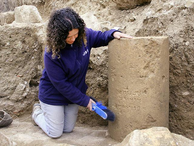 IAA archaeologist Danit Levy examines the 2,000 year-old inscription of 'Jerusalem', Photo, IAA, Yoli Shwartz