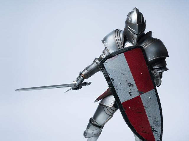 knight in full armour holding a shield and a sword
