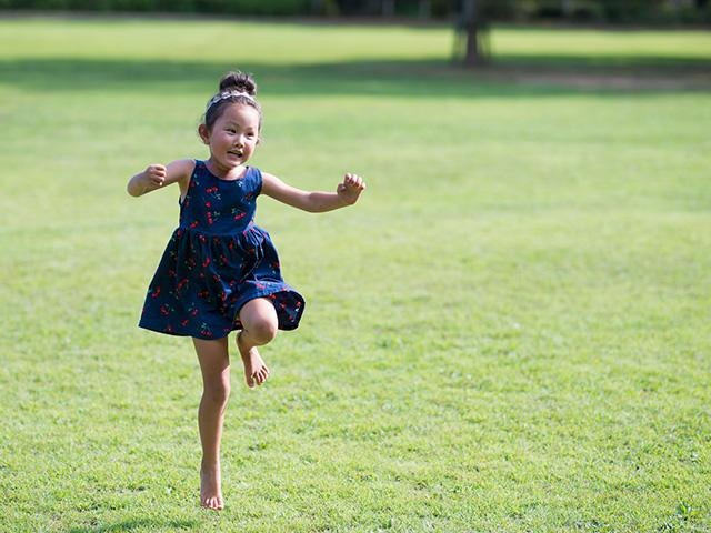 little girl skipping in the green grass