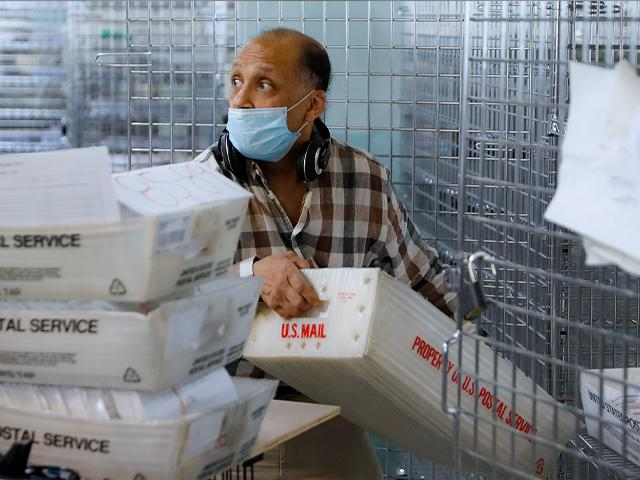 A worker gathers ballots from security cages before they are checked at a Board of Elections facility, Wednesday, July 22, 2020, in New York. (AP Photo/John Minchillo)