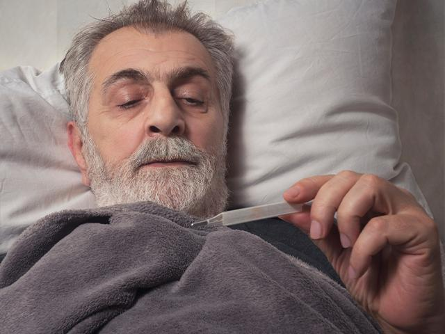 man in bed looking at a thermometer