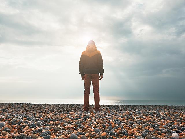 man standing on rocky coast