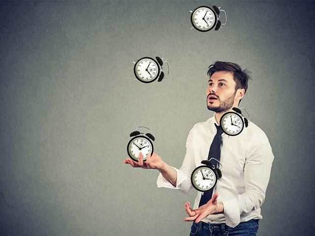 man juggling clocks